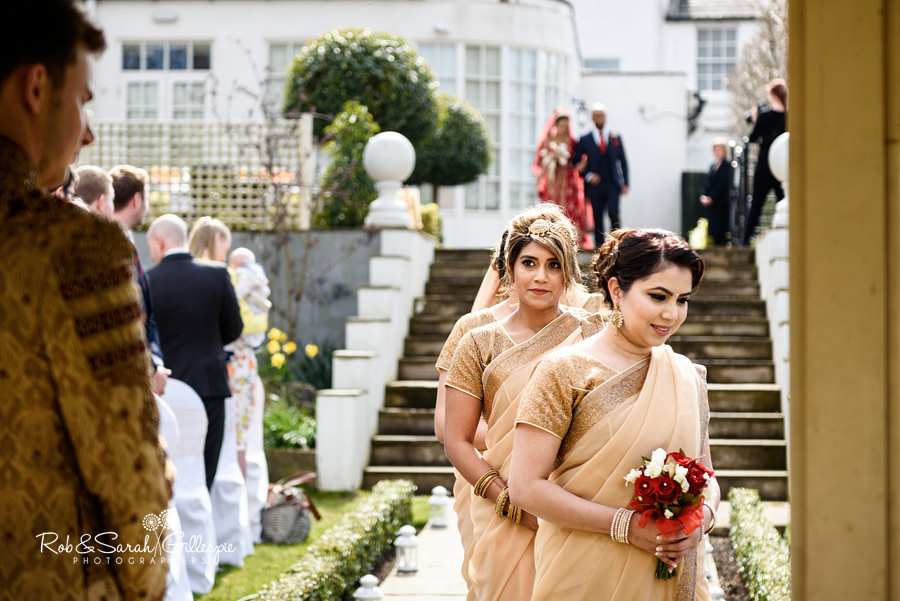 Bridesmaid looks at Groom as she walks up aisle during outdoor service at Warwick House