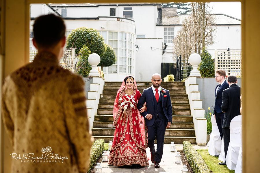 Bride walks towards groom smiling, at Warwick House