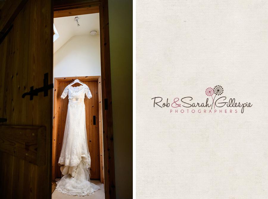 Lace wedding dress hanging in doorway