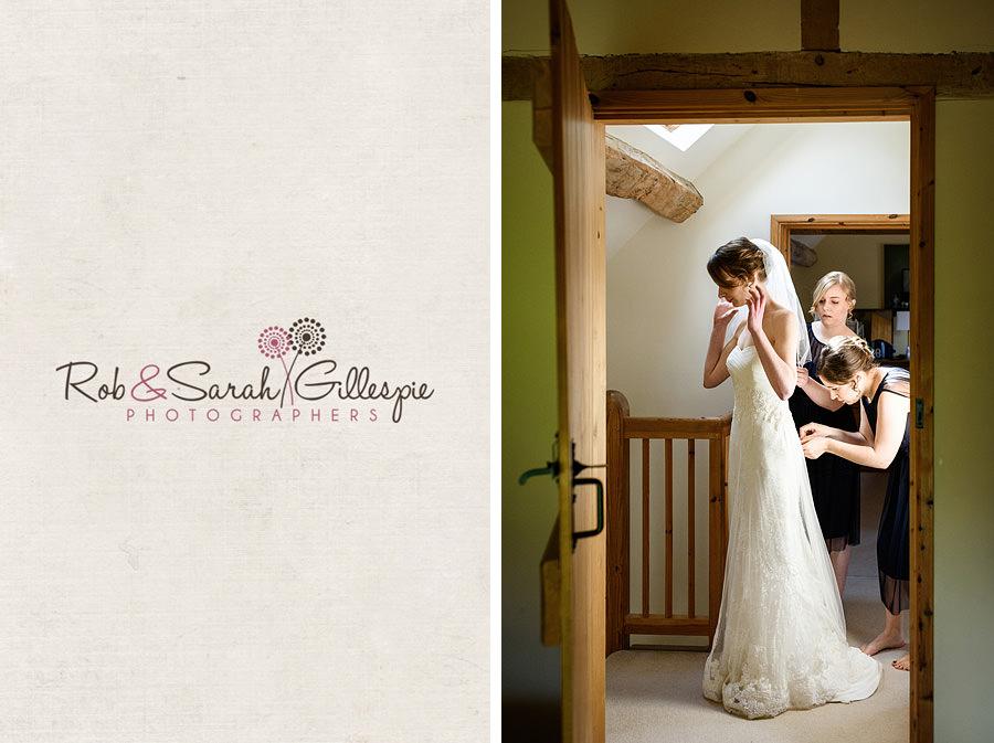 Bride has dress fastened by bridesmaids in hallway