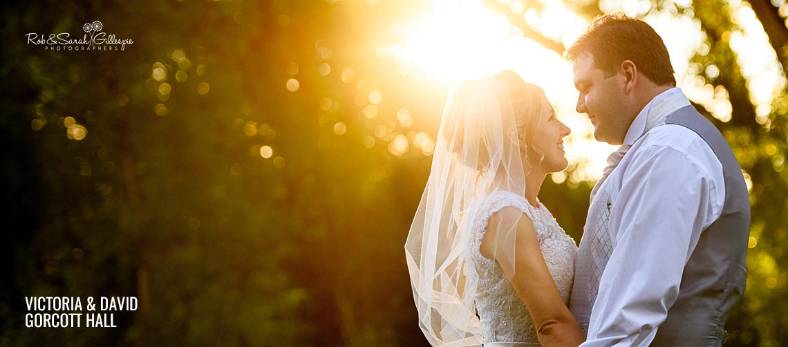 Bride and groom in Gorcott Hall grounds with stunning sunset
