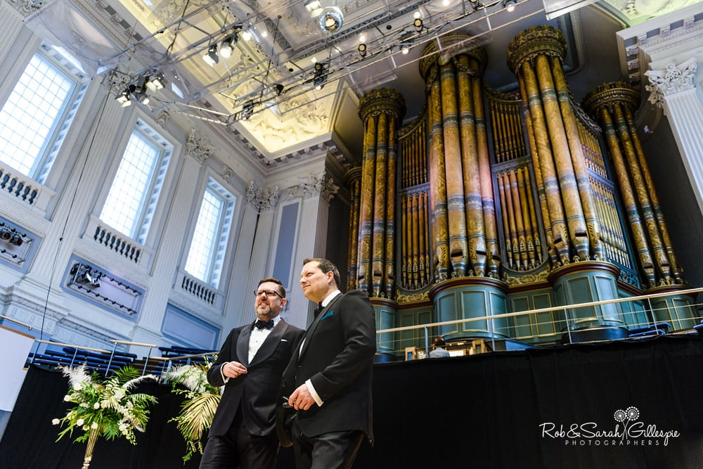 Dramatic photo of groom and best man waiting for guests at Birmingham Town Hall with pipe organ in background
