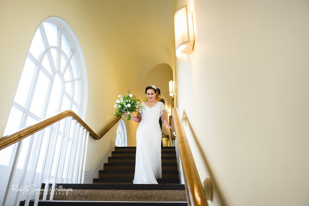 Brides walks down stairway at Birmingham Town Hall