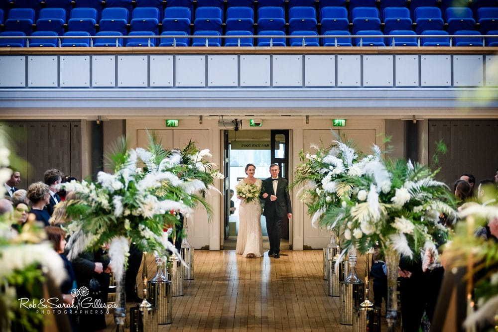Bride and father make entrance to wedding ceremony inside Birmingham Town Hall