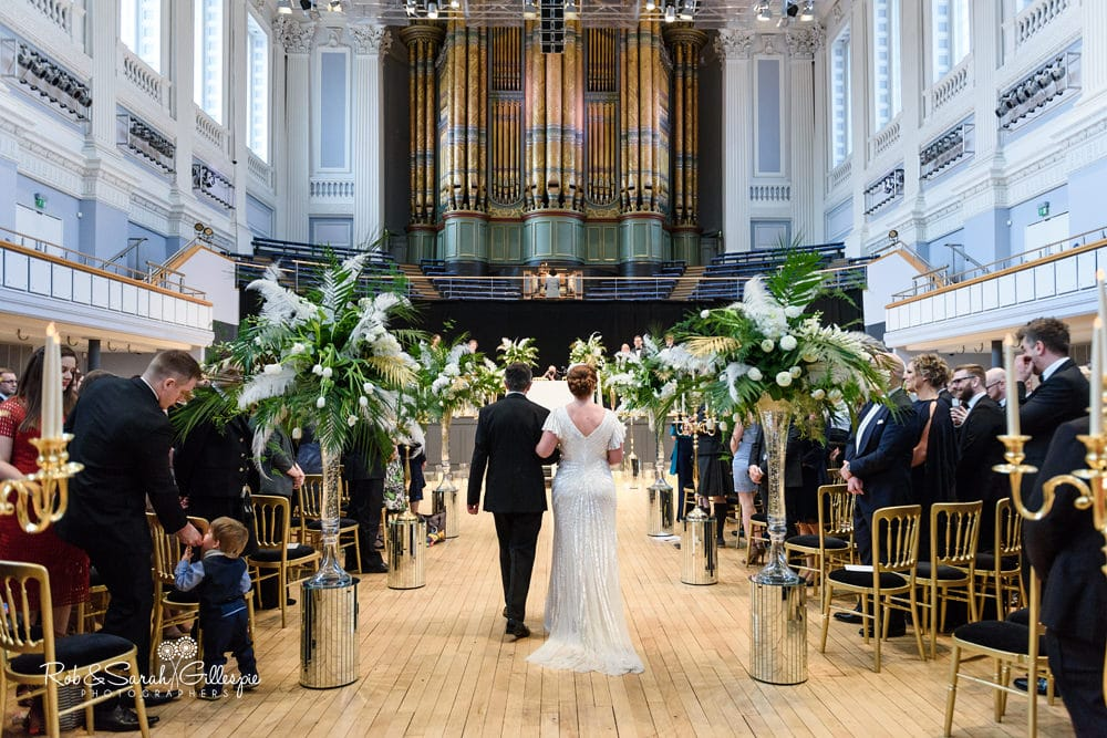 Bride and father make entrance to wedding ceremony inside Birmingham Town Hall, with guests watching