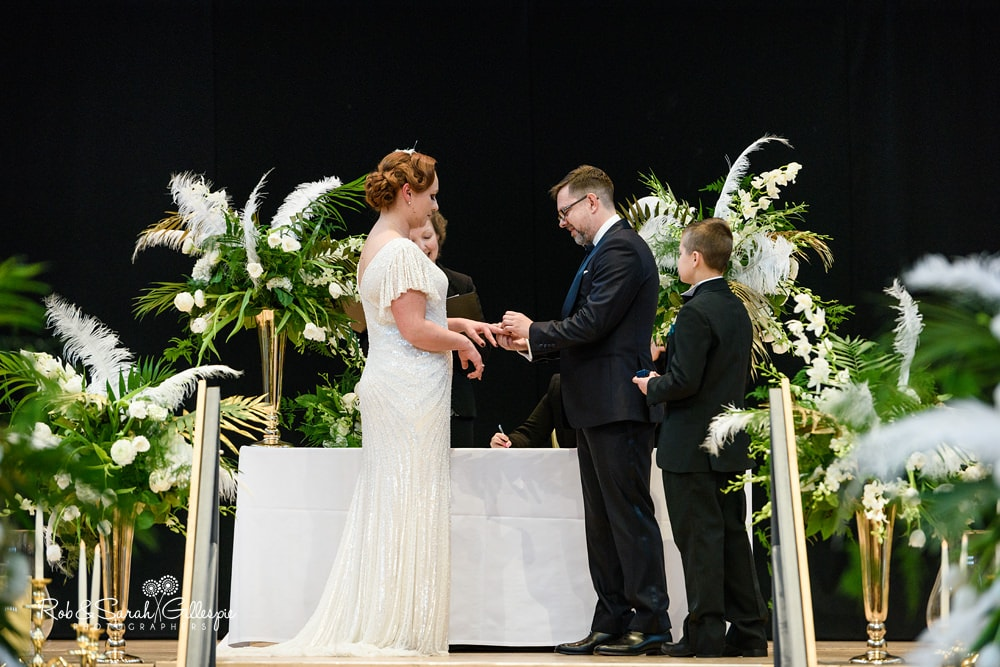 Bride and groom exchange rings during Birmingham Town Hall wedding ceremony