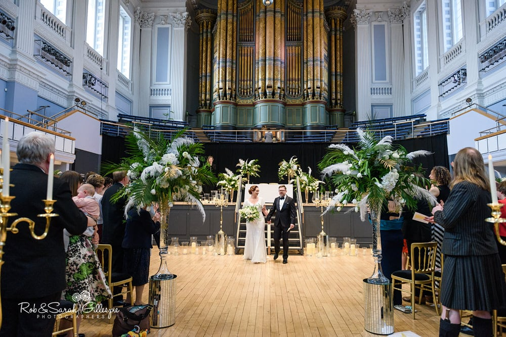 Bride and groom walk up aisle at end of Birmingham Town Hall civil wedding ceremony