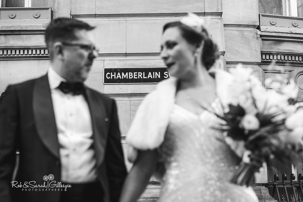 Bride and groom stand underneath sigh for Chamberlain Square near Birmingham Town