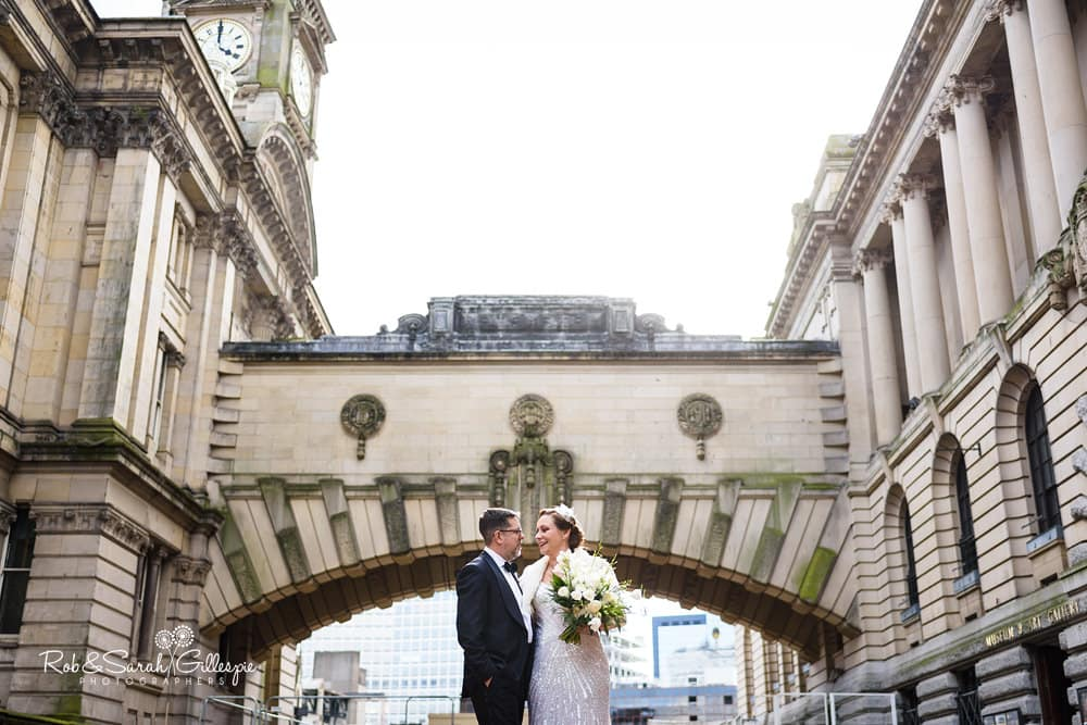 Bride and groom together underneath Birmingham Museum and Art Gallery arched bridge