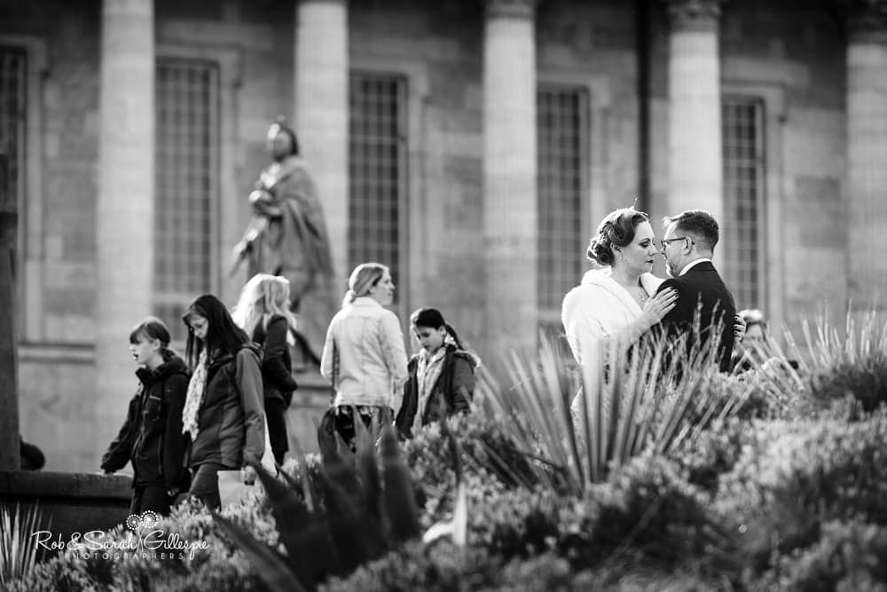 Bride and groom in Victoria Square with Birmingham Town Hall in background as crowds walk on by