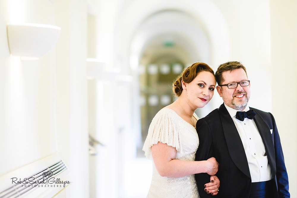 Stylish bride and groom pose for photo in Birmingham Town Hall corridor