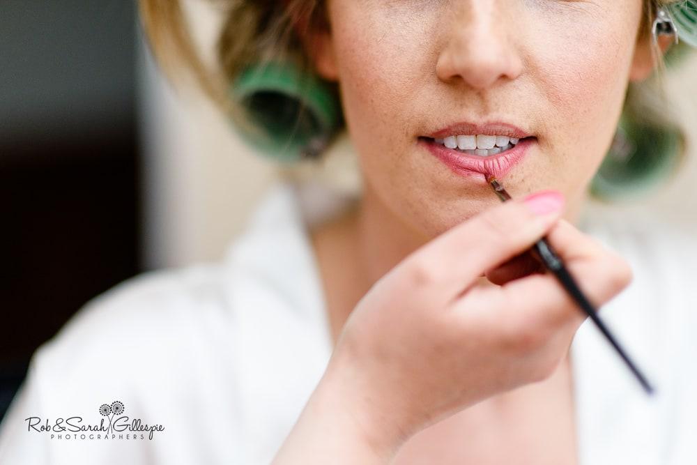 Close up of bride having lip gloss applied
