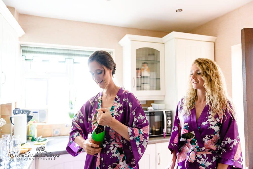 Bridesmaids open champagne bottle