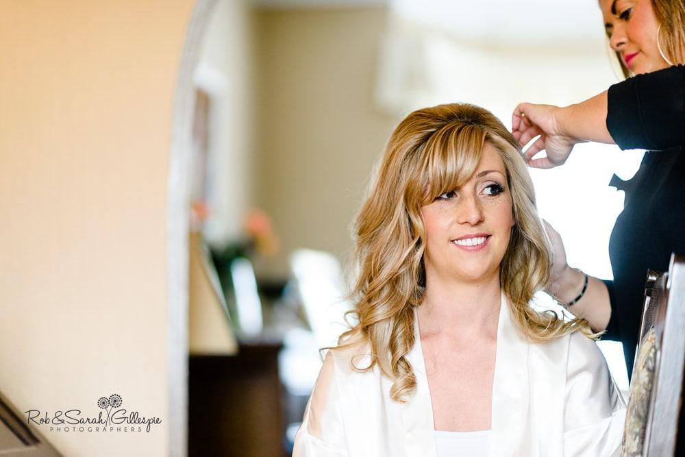 Bride having hair styled brefore wedding