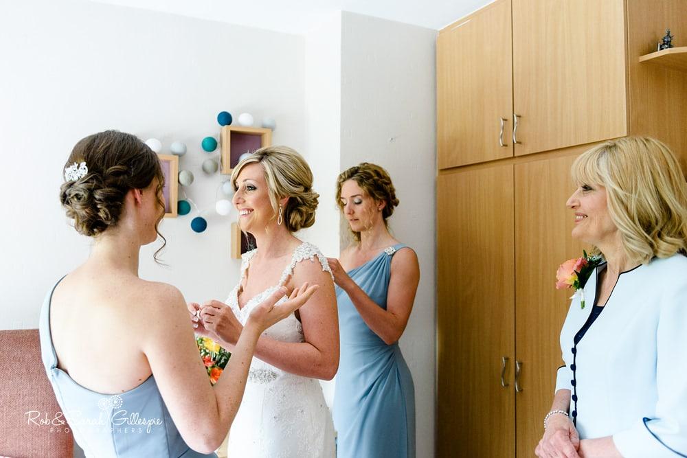 Bride has wedding dress fastened