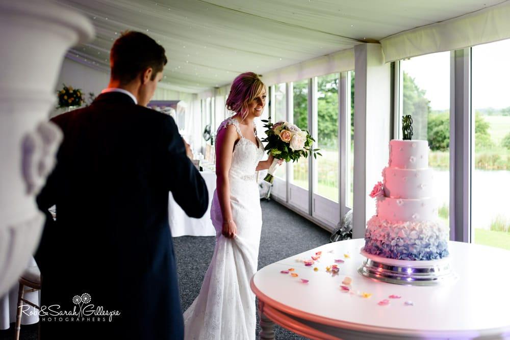 Bride and groom look at wedding cake at Alrewas Hayes