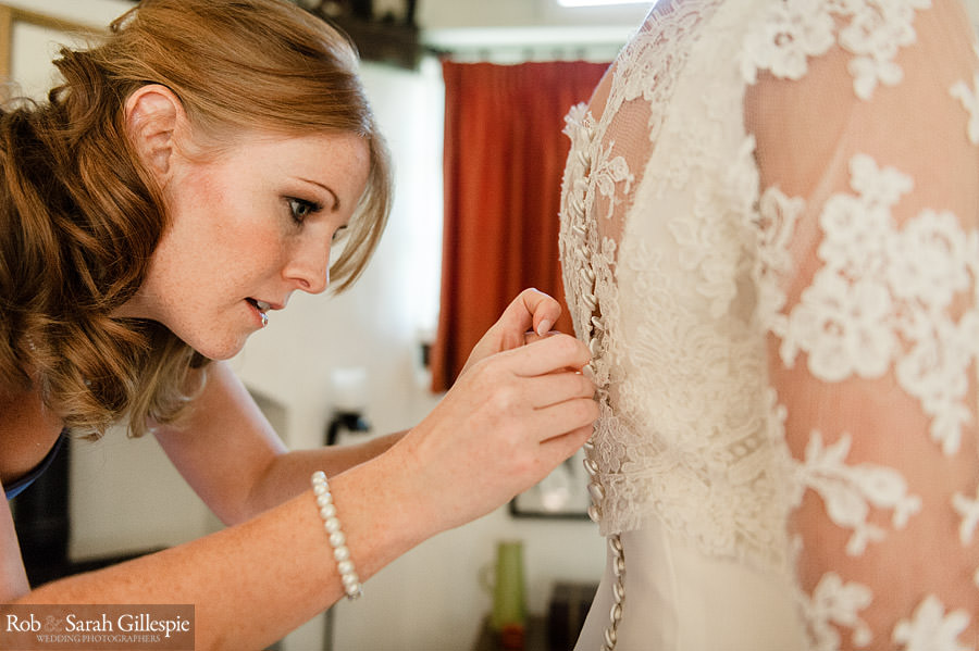 Photo of bridemaid side-on while she fastens brides dress