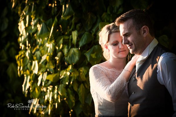 Bride and groom in doorway at Nuthurst Grange surrounded by ivy