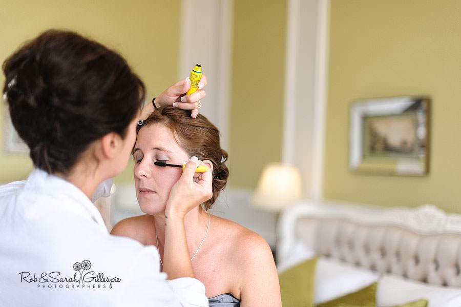 bride helping bridesmaid with makeup