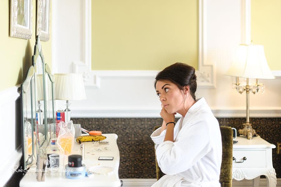 bride sitting down fixing earrings
