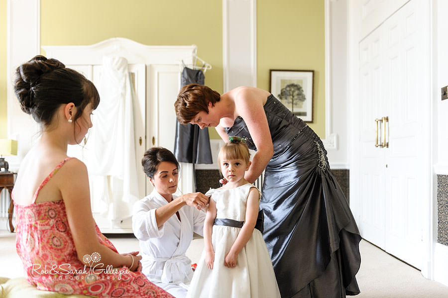 bride and bridesmaids helping flowe girl into dress