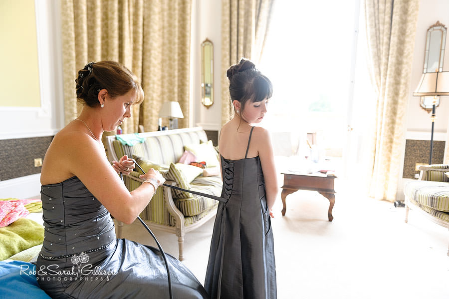 bridesmaid helping young bridesmaid with dress