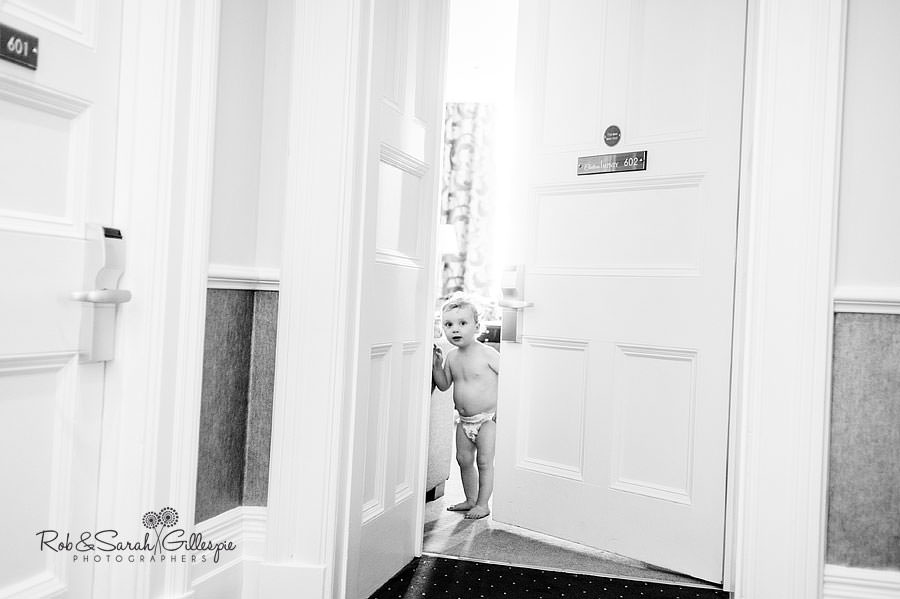 young pageboy peeking through hotel door