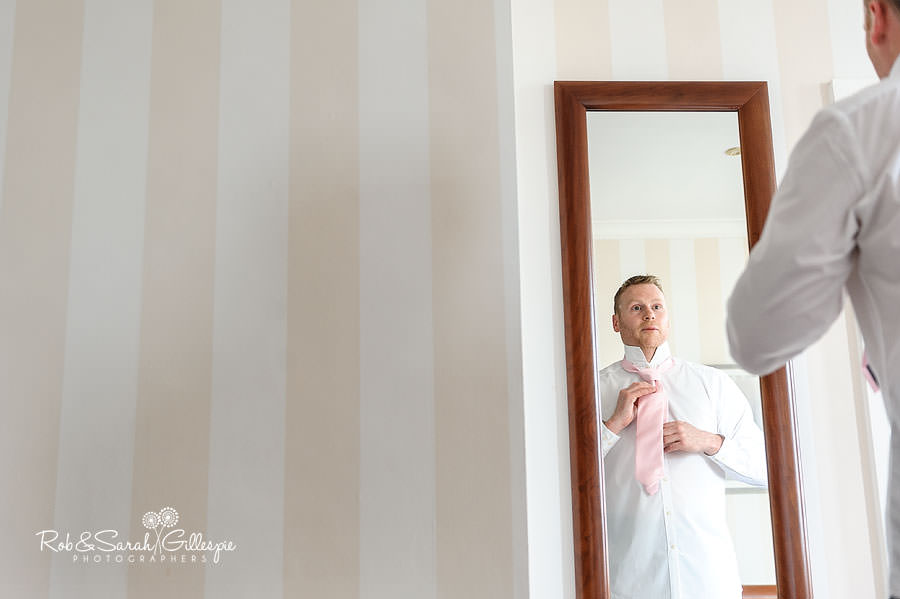 groom putting on tie in chateau impney room