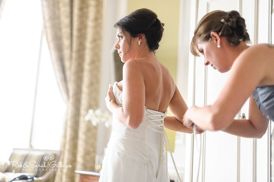 bridesmaid tightening wedding dress with bride