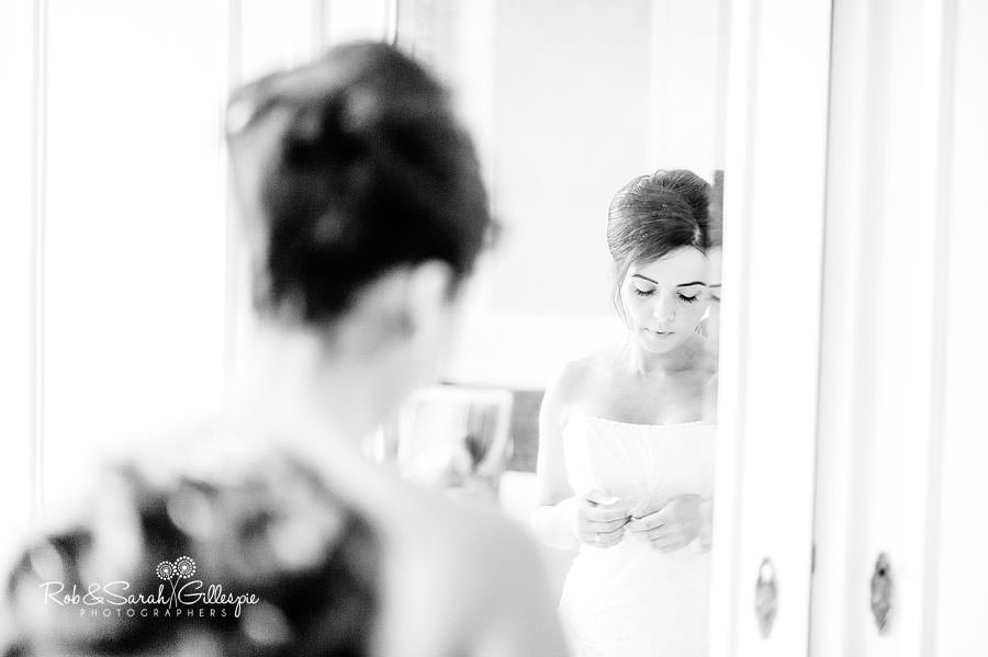 bride in mirror as wedding dress is tied up
