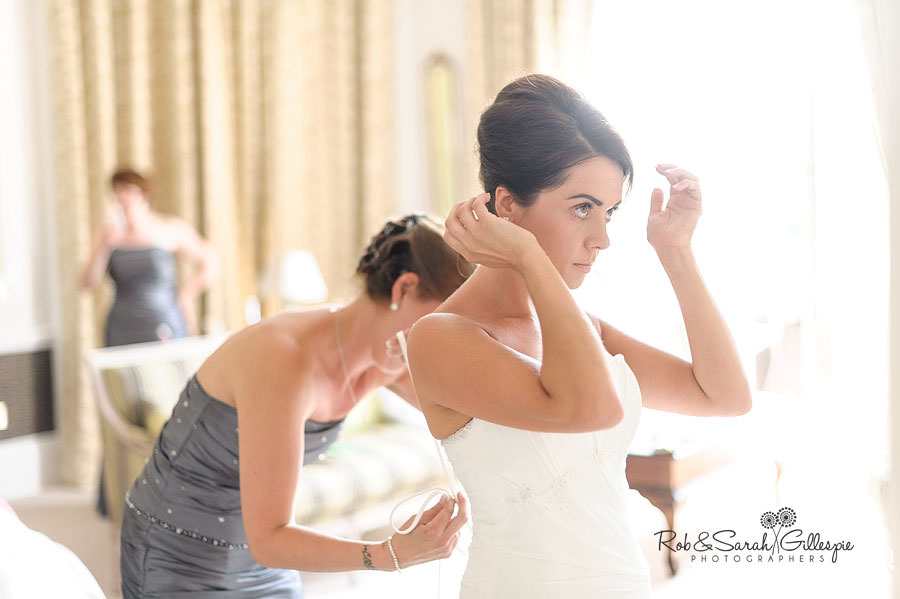 bride fixing hair in mirror while dress is tied up