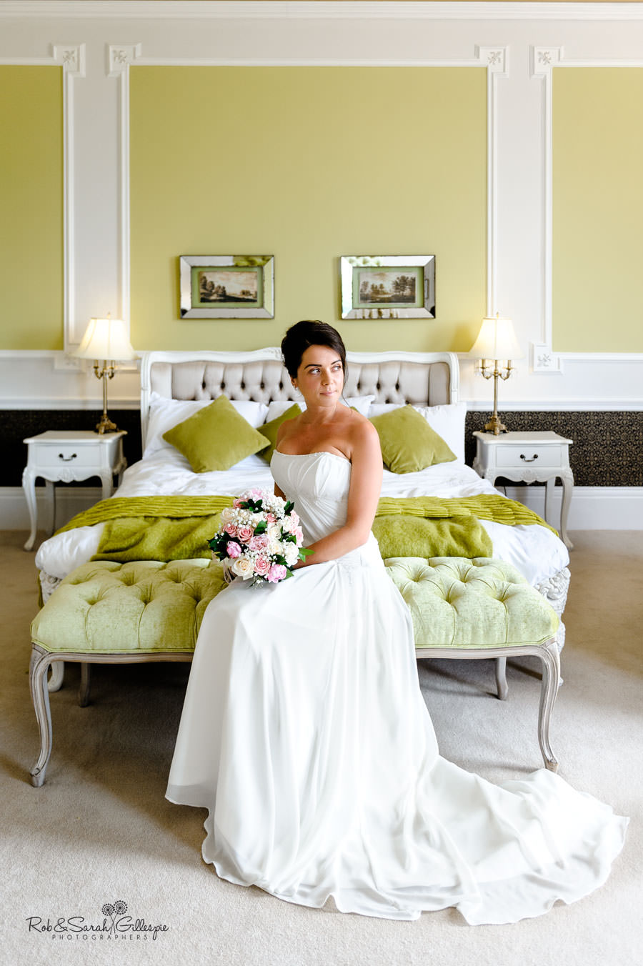 bride portrait sitting on bed in grand room at chateau impney