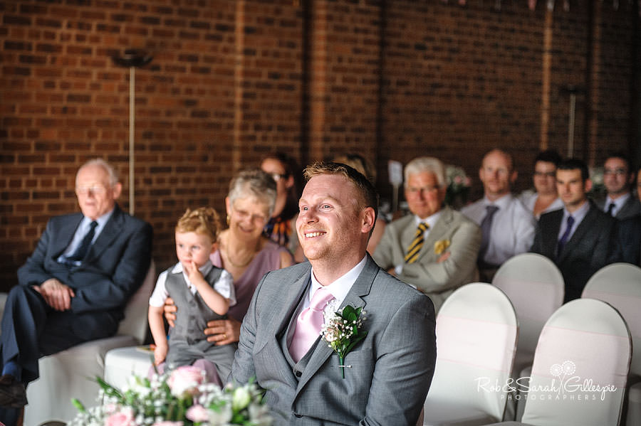nervous groom smiles waiting for bride
