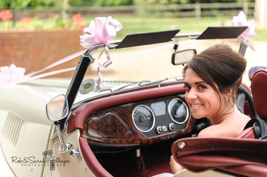bride smiling in morgan wedding car