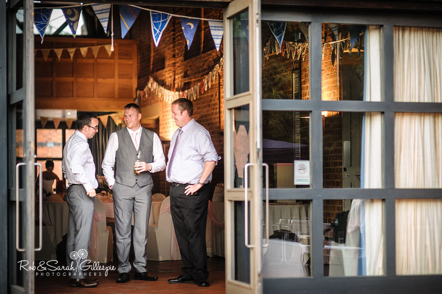 groom and guests chat during wedding reception at avoncroft museum