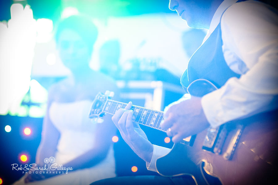 groom plays guitar for bride at wedding