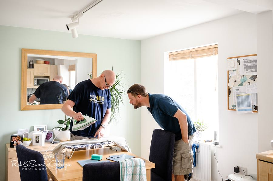 groom and best man trying to iron clothes for wedding