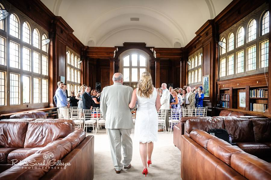 bride and father walk up the aisle inside malvern college memorial library