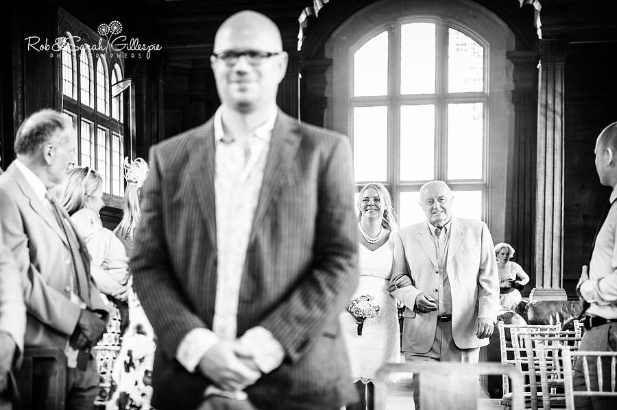 bride walking up the aisle inside the memorial library at malvern college