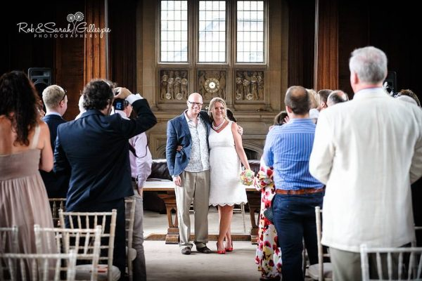 Bride and groom face their guests after getting married at Malvern College Memorial Library
