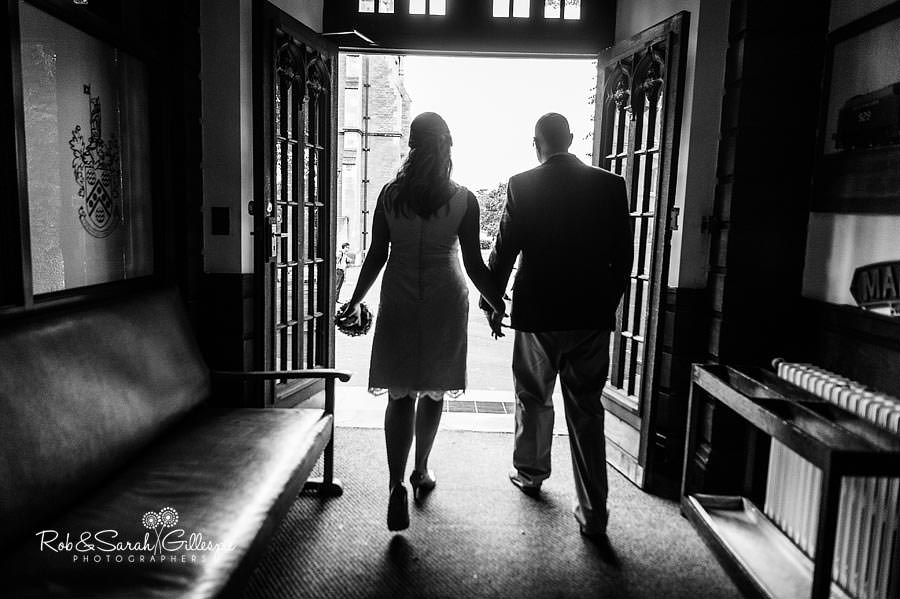 bride and groom walking hand in hand our of malvern college memorial library