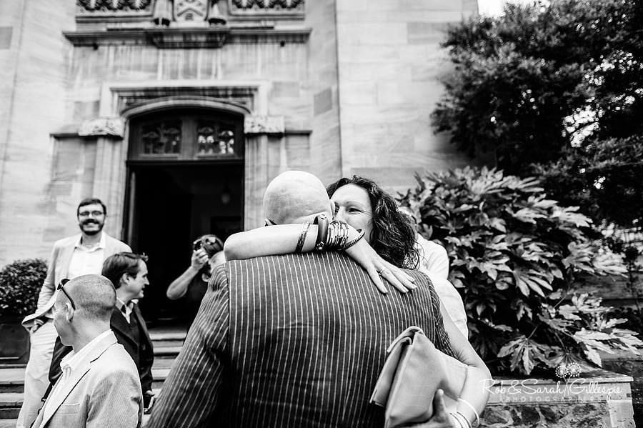 guest hugs groom after wedding service outside memorial library