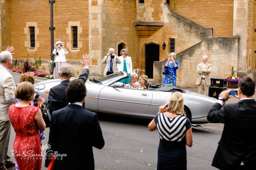 bride and groom waved off by guests