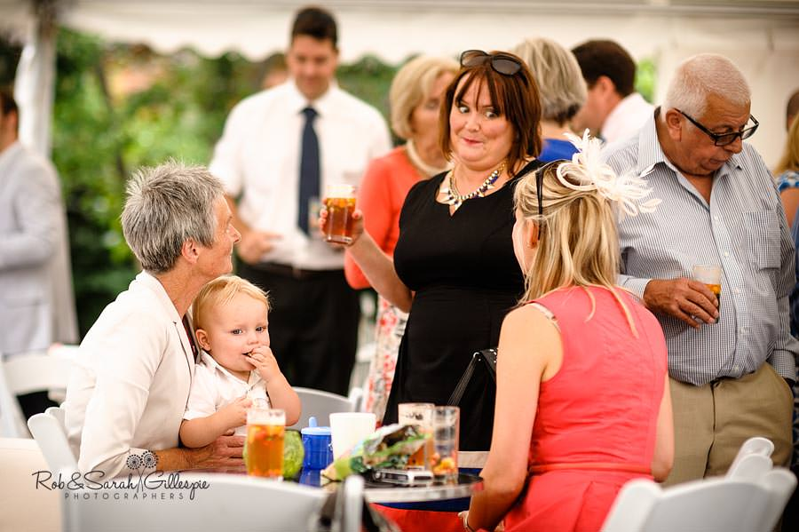 wedding guests relaxing at marquee reception