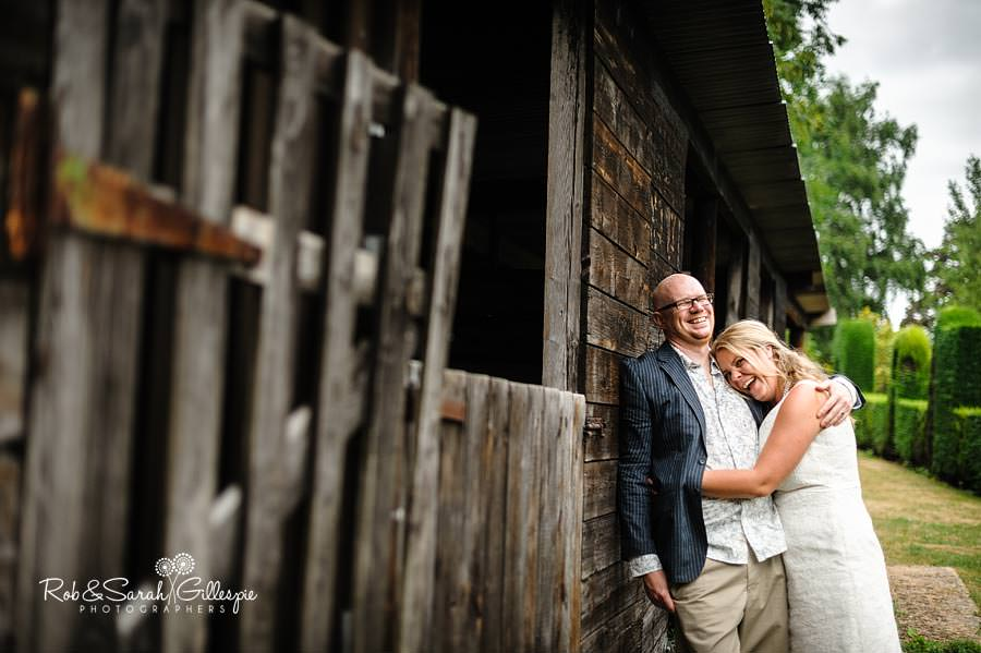 bride and groom laughing outside stables