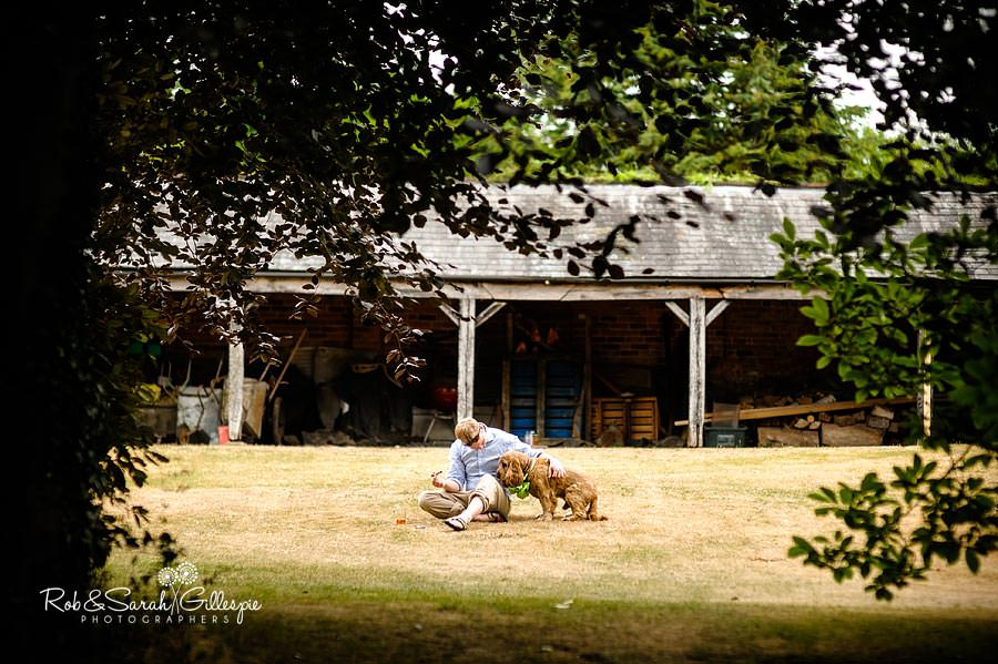 guest playing with dog at wedding reception