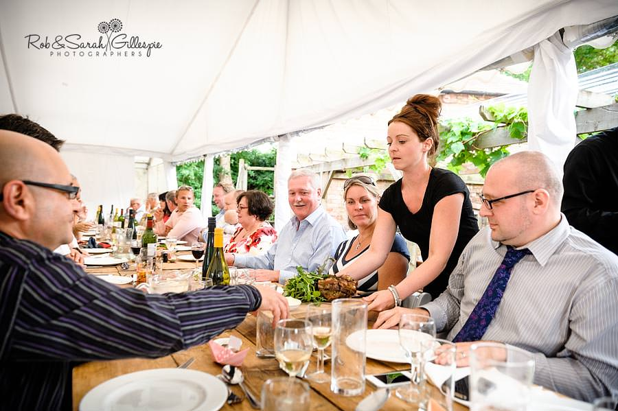 staff serve main course at wedding reception in marquee