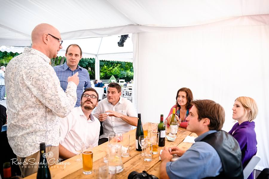 groom and wedding guests relaxing in marquee