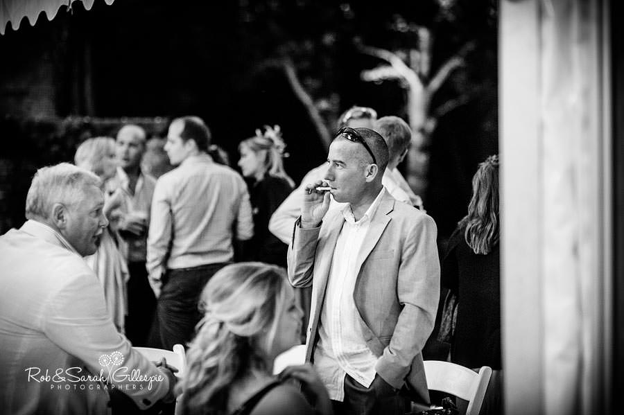 guest relaxes with cigarette at wedding reception