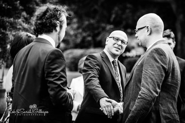 Groom greets wedding guests at Malvern College Memorial Library